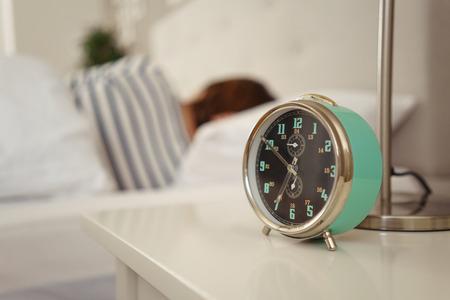 Wekker gaat rinkelen naast een slapende persoon in bed met de nadruk op het nachtkastje advertentie klok Stockfoto