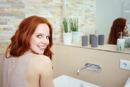 limpieza: Cabeza y hombros Vista posterior de la mujer atractiva joven con el pelo rojo El uso de ropa interior de encaje Mirando hacia atrás y sonriendo por encima del hombro en el baño con lavabo y un espejo en el fondo Foto de archivo
