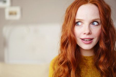 Head and Shoulders Portrait of Young Woman with Long Red Hair Wearing Yellow Sweater and Looking to the Side Playfully in Bedroom with Copy Space Stockfoto