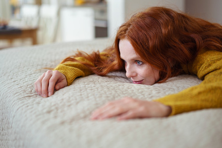 Close Up of Smiling Contented Young Woman with Red Hair Wearing Yellow Sweater Lying on Stomach on Comfortable Bed with Textured Duvet Stok Fotoğraf