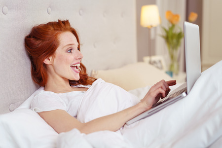 looking at computer: Side Profile View of Happy Young Woman with Red Hair Looking Surprised and Elated While Using Laptop Computer in Comfortable Bed with Plush Duvet in Luxury Hotel Bedroom Stock Photo