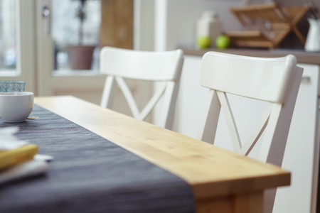 dining table and chairs: Two empty chairs at a dining table in a house or apartment, selective focus to the one in the foreground