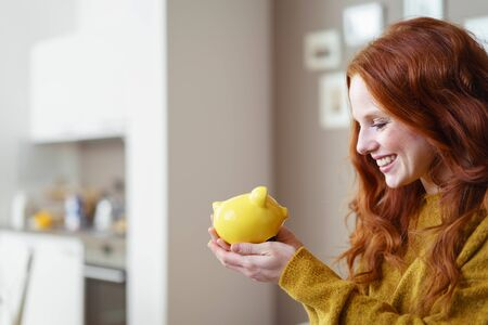 bank interior: Young woman smiling happily at her yellow ceramic piggy bank she is holding in her hands as she anticipates spending her nest egg