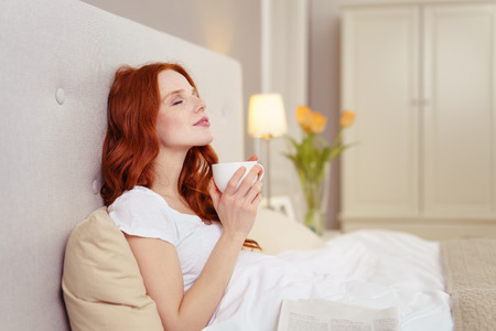 Side Profile View of Young Woman with Red Hair Enjoying Coffee in Bed with Head Leaning Back Against Headboard and Looking Blissful in Luxury Hotel Bedroom Imagens