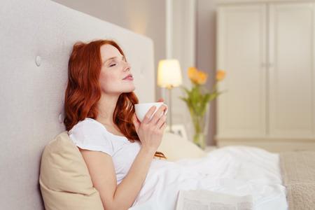 Vista lateral del perfil de la mujer joven con el pelo rojo goza de café en la cama con la cabeza de la espalda apoyada en la cabecera y buscando dichoso en dormitorio del hotel Foto de archivo