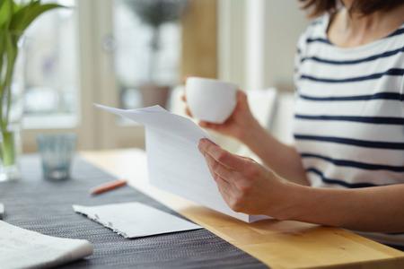 Frau liest ein Dokument am Esstisch, als sie eine Tasse Kaffee am Morgen genießt, Nahaufnahme von den Händen