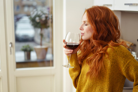 tomando vino: Young redhead woman standing in her apartment sipping a glass of red wine with her eyes closed in pleasure, side view