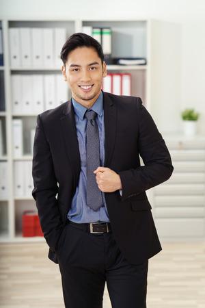 hombres trabajando: Un solo hombre de negocios joven feliz en traje oscuro y corbata haciendo un gesto con el puño cerrado mientras está de pie delante del estante en la oficina