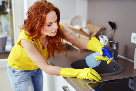 apartment cleaning: Attractive young redhead woman cleaning the kitchen at home spraying the surfaces with detergent from a spray bottle