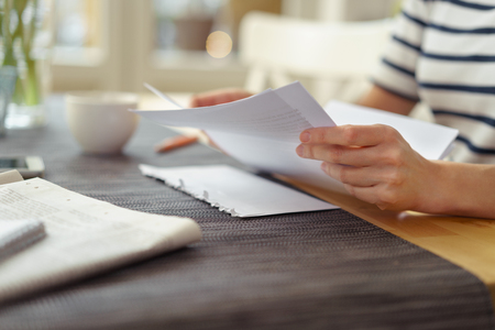 documents: Person seated at a table with a cup of coffee reading a paper document, close up view of the hands