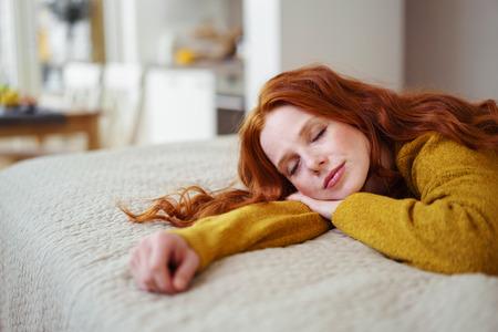 Mooie jonge redhead vrouw die een dutje als ze besteedt een ontspannende dag thuis liggend op haar buik op haar bed Stockfoto