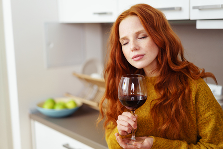 Pretty young woman relaxing with a glass of red wine standing with her eyes closed in bliss leaning against a kitchen counter at home Imagens