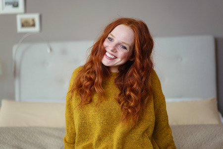 red haired: Gorgeous young redhead woman sitting on her bed looking at the camera with a warm friendly smile