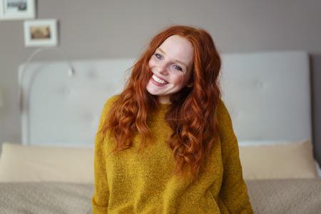Superbe jeune femme rousse assise sur son lit en regardant la caméra avec un sourire chaleureux
