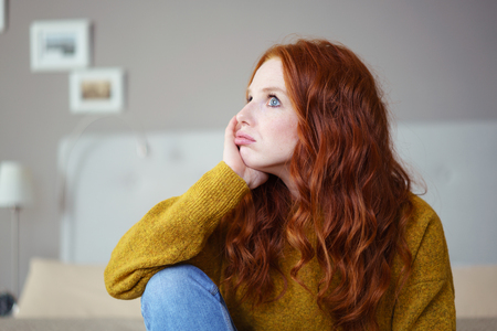 yellow fleece: Pretty young redhead woman sitting on her bed with her chin on her hand pouting her lips with a glum expression a s she stares into the distance Stock Photo