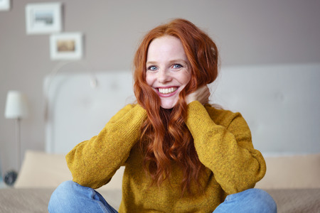 red haired: Laughing pretty red haired female in yellow sweater playing her hair while laughing and sitting on bed