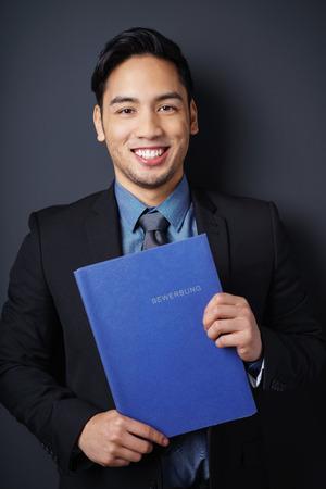 Succesvolle jonge Aziatische zaken sollicitant houdt zijn CV in een blauwe map op zijn borst als hij glimlacht gelukkig bij de camera