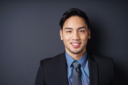 Primo piano sorridente di singolo giovane manager di sesso maschile con la barba in giacca blu, camicia e cravatta con copia spazio a sfondo scuro