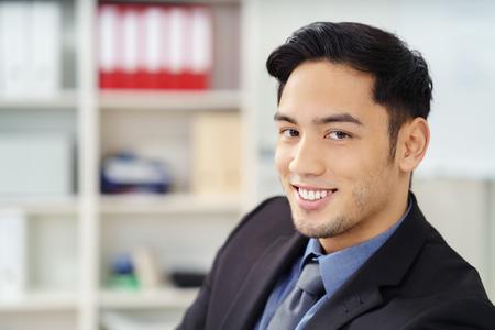 Close-up van lachende jonge Aziatische zakenman in zwart blazer jas en blauwe overhemd met stropdas in de voorkant van verduisterde boekenrek op kantoor Stockfoto
