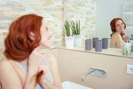 domiciles: Head and Shoulders of Attractive Young Woman with Red Hair Smiling and Admiring Reflection in Mirror in Luxury Bathroom Stock Photo
