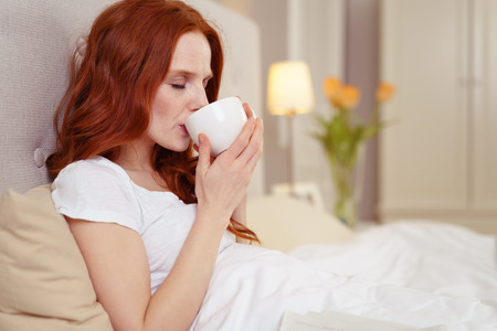 Side Profile View of Young Woman with Red Hair Enjoying Morning Coffee in Bed in Luxury Hotel Bedroom - Sipping Warm Liquid from Mug with Eyes Closed