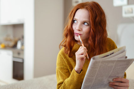 musing: Thoughtful young woman doing a cryptic crossword puzzle in a newspaper looking off to the side with a pensive expression as she tries to solve a clue