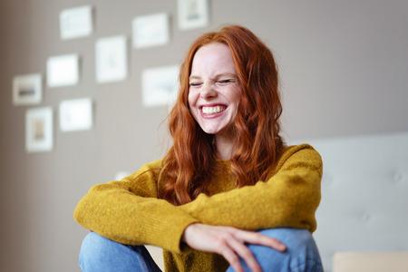 Довольно оживленная молодая женщина смеется с ее глаза закрыты резьбовыми в откровенном момент веселья и веселью, как она сидит на кровати у себя дома Фото со стока
