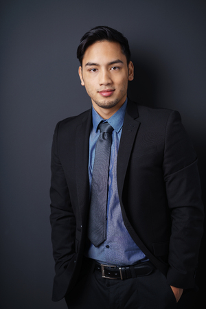 asian business man: Calm adult male corporate executive in dark blazer jacket and tie with hands in pockets leaning against black background with copy space