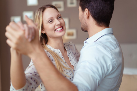 Leuke gelukkige jonge vrouw die van een dans in de armen van haar man geniet terwijl zij een speciale gelegenheid bij het huis vieren, close-up hoofd en schouders bekijken