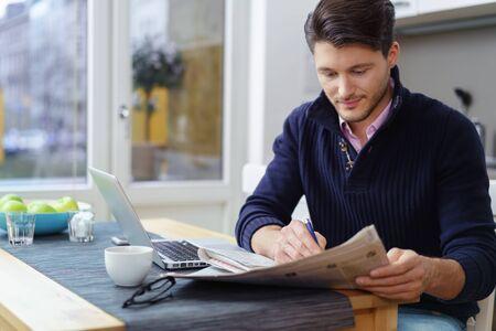 自宅に彼の台所のテーブルに座っている若い男が雇用または宿泊施設の新聞に広告を検索