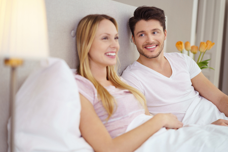 fond: Vivacious young woman watching television propped up against the pillows in bed as her husband looks on with a fond smile