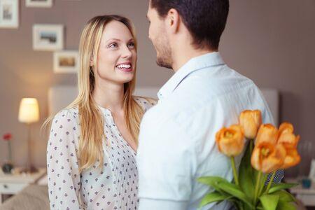 pareja en casa: El hombre joven romántico que da a su esposa un regalo sorpresa que oculta un ramo de tulipanes amarillos frescas detrás de su espalda, se centran en la cara sonriente Foto de archivo