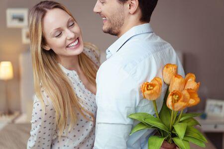sorpresa: El hombre joven no tan bueno en mantener en secreto la esperanza de dar un regalo sorpresa de flores a su novia, pero ella est� mirando por encima de los hombros de espionaje a cabo los tulipanes ocultos