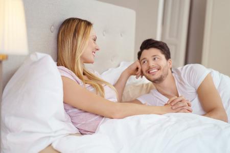 parejas sensuales: joven pareja romántica en la luna de miel se relaja en la cama mirando con ternura a los ojos mientras mantiene las manos