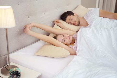 enamorados en la cama: Pareja joven que despierta en cama en la madrugada de estiramiento y sonriente con expresiones serenas y los ojos cerrados