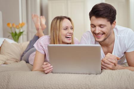 enamorados en la cama: feliz pareja de jóvenes riendo de algo en la web, ya que relajarse juntos acostado en una cama descalza