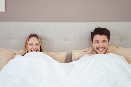 peer to peer: Playful young couple lying in bed grinning with happiness as they peer over the white duvet while celebrating their honeymoon on vacation
