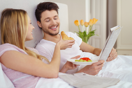 wake: Happy young couple sharing breakfast in bed as the young woman offers her husband a bite from a croissant bread roll