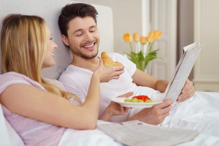 despertarse: joven pareja que comparte el desayuno en la cama mientras la joven ofrece su marido una mordedura de un rollo de pan croissant