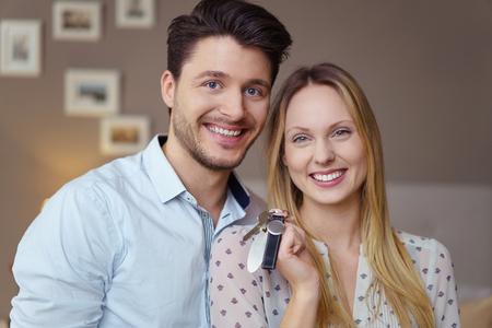 행복 한 젊은 부부 키 또는 새 집 또는 아파트 서 행복 하 게 웃 고 카메라를 행복 하 게 흥분된 머리와 어깨를 닫습니다. 스톡 콘텐츠