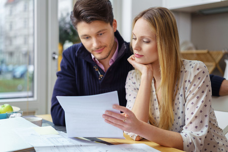 Handsome young man with mustache and beautiful woman with long hair at table looking at documents in kitchen next to window Archivio Fotografico