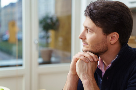 contemplates: Thoughtful man sitting with his chin resting on his hands staring out of a window as he daydreams or contemplates a problem