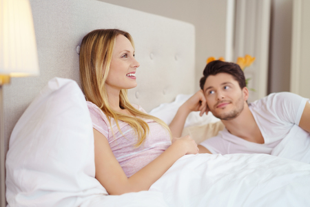 parejas de jovenes: Young woman captivated by the television sitting propped against the pillows in bed watched from the side by her smiling long suffering husband