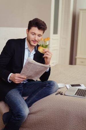munching: Young businessman working in a hotel bedroom sitting on the edge of the bed reading a document and munching on a snack