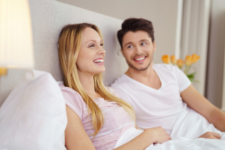 adoring: Young woman enjoying a television program lying in bed laughing watched by her adoring husband lying alongside her