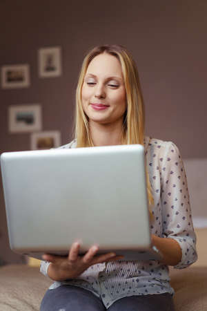 handholding: Young woman smiling in amusement as she sits handholding her laptop computer and reading the screen indoors at home