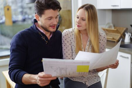couple home: Young couple planning for a new home standing in a kitchen holding blueprints of a new design or renovation