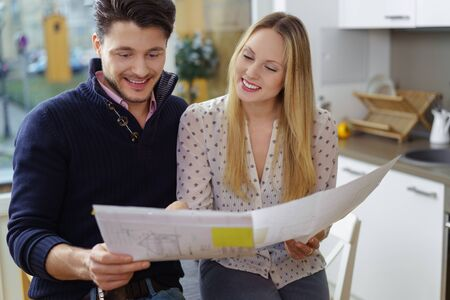 two hands: Excited young couple making plans for a new home standing in a kitchen holding blueprint designs for a renovation or new build Stock Photo