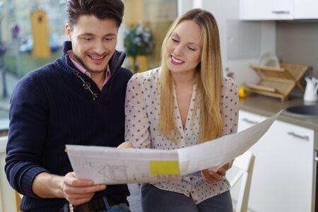 Podekscytowany młoda para podejmowania planów nowego domu stoi w kuchni gospodarstwa wzorów plan na remont lub nowobudowanych