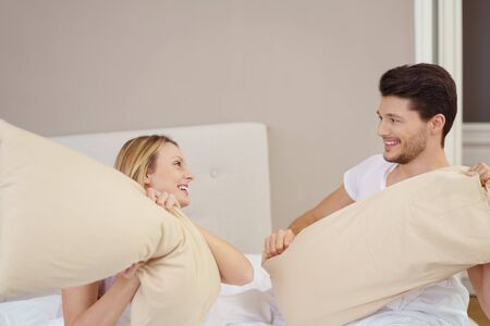 sexy lovers: Fun young couple enjoying a pillow fight in their bedroom at home laughing as they hit each other with their pillows